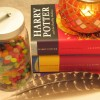 harry potter book next to jar of jellybeans, candle, and feather
